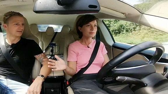 Janett hebt die Hände vom Lenkrad des autonomen Fahrzeugs.