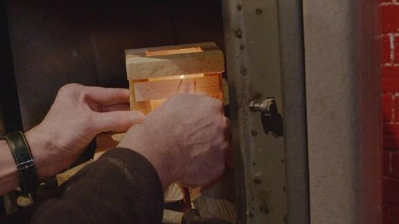 Ein Ofen wird mit Hilfe einer Feueranzünder-Box angefeuert.