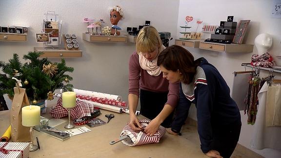 Janett Eger packt zusammen mit Annett Gerhardt Geschenke ein.
