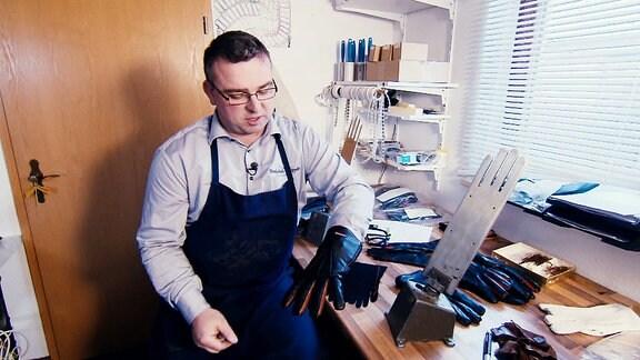 Ein Handschuhmacher zeigt in seiner Werkstatt einen Lederhandschuh mit Fingerheizung.