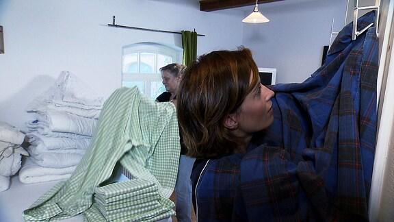 Janett Eger probiert eine Vorrichtung aus, die beim Bettbeziehen helfen soll.