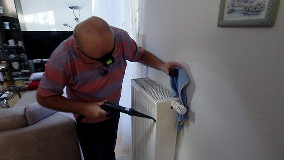 Ein Mann mit einer Stirnlampe reinigt mit einem Dampfreiniger einen Heizkörper.