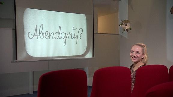 """Henriette sitzt in einem Kinosessel vor einer Leinwand, auf der der Schriftzug """"Abendgruß"""" aus dem Sandmann zu lesen ist."""