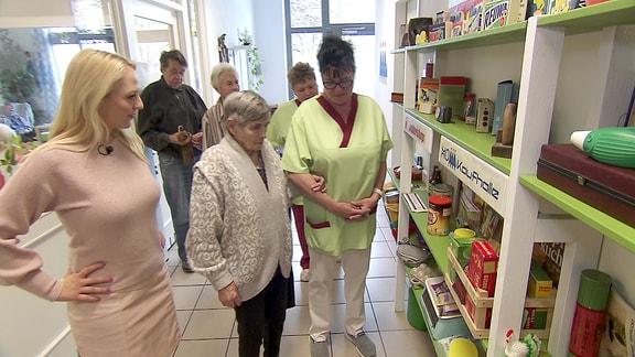 Moderatorin Henriette Fee Grützner steht mit Bewohnerinnen und Betreuerinnen eines Altenheims vor einem Regal mit DDR-Gegenständen.