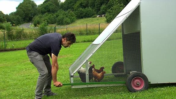 Ein Mann bewegt einen fahrbaren Kleintierstall, in dem er Hühner hält.