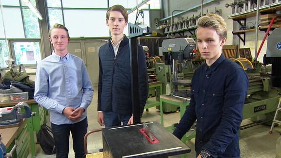 Drei Abiturienten stehen in einer Werkstätten an einer Kreissäge.
