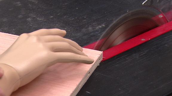 Das Modell einer Hand wird in Richtung eines rotierenden Kreissägeblatts geschoben.