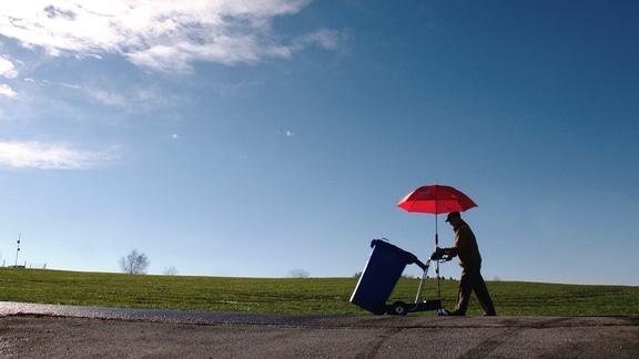 Ein Mann transportiert eine Mülltonne mit einer elektrisch betrieben Karre, an der sich ein roter Sonnenschirm befindet.