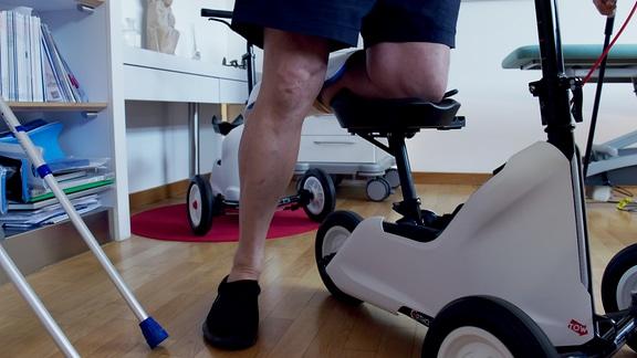 Ein Mann legt sein Knie auf einen speziellen Roller für Menschen mit Beinproblemen.