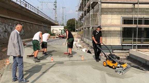 Drei Arbeiter kehren Pflaster mit Besen ein, einer mit einer speziellen Maschine.