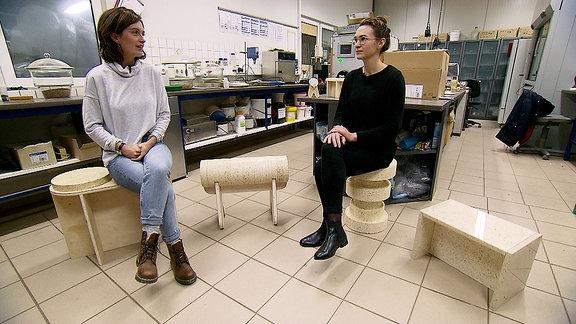 Janett Eger sitzt mit einer anderen Frau in einem Labor auf Sitzmöbeln aus gepresstem Popcorn.