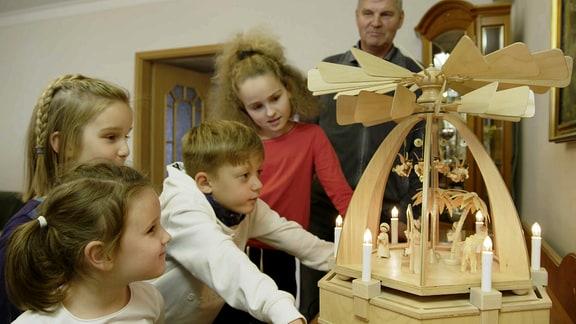 Kinder bestaunen eine Weihnachtspyramide.