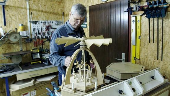 Ein Mann baut in einer Werkstatt eine Weihnachtspyramide.