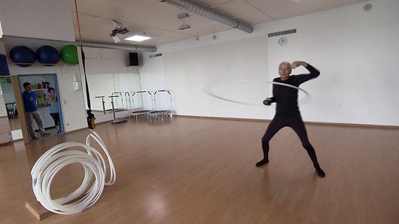 Ein Mann trainiert mit einem variablen Hula-Hoop-Reifen.