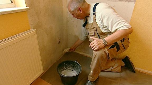 Ein Mann behandelt eine Wand mit einem Schimmelmittel.