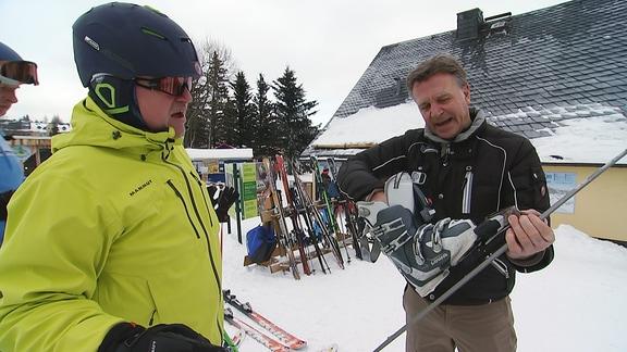 Ein Mann führt einem Skifahrer seine Skischuh-Skibindungs-Kombination vor.