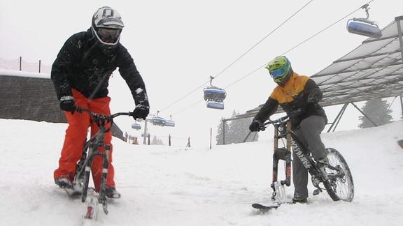 zwei Männer Fahrrädern mit Kurzski anstelle der Voderräder im Schnee