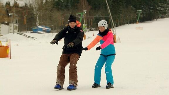 Janett Eger lässt sich von einem Mann zeigen, wie man mit Snowskates fährt.