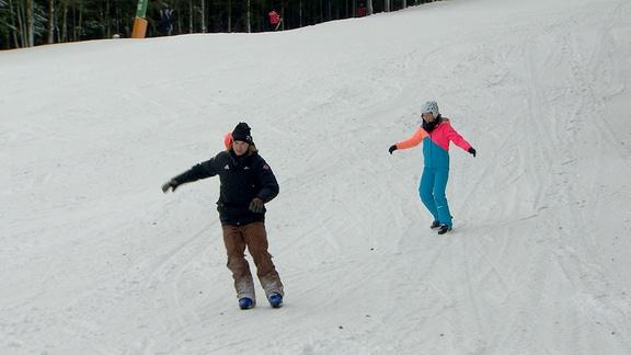 Janett Eger fährt auf Snowskates einen Schneehang runter.