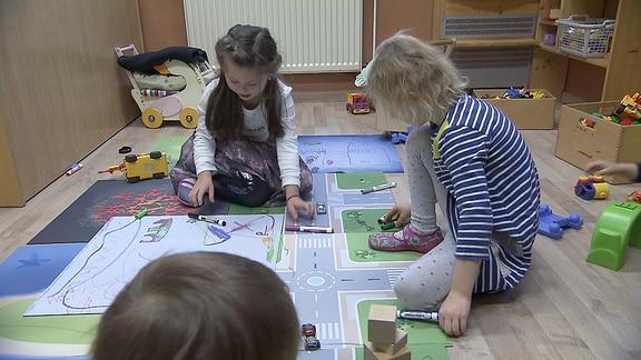 Kinder sitzen auf bunten Matten und spielen.