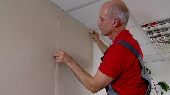 Ein Mann bringt Flachstapete an die Wand.
