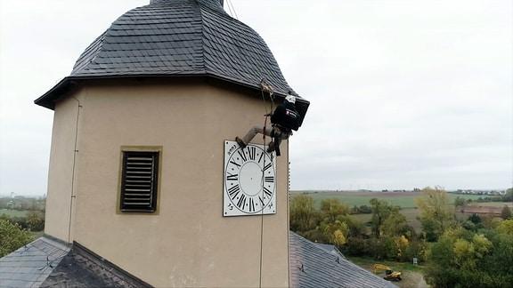 Ein Mann seilt sich an einem Kirchturm ab, um eine Turmuhr zu installieren.