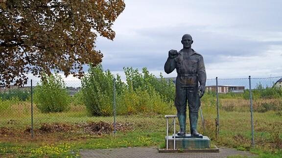 Statue eines Mannes vor einem eingezäunten Gelände