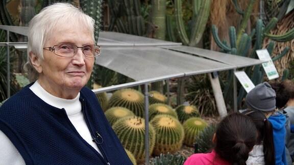 Alte Frau in Gewächshaus, neben ihr stehen Kinder