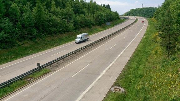 Ein weißer Kleintransporter fährt auf einer Autobahn.