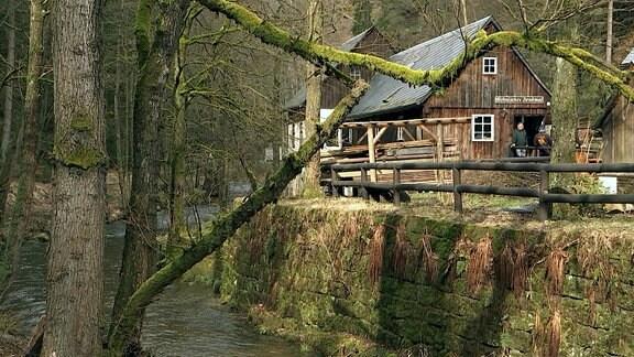 Blick auf ein altes Haus, daneben abwärts fließt Wasser