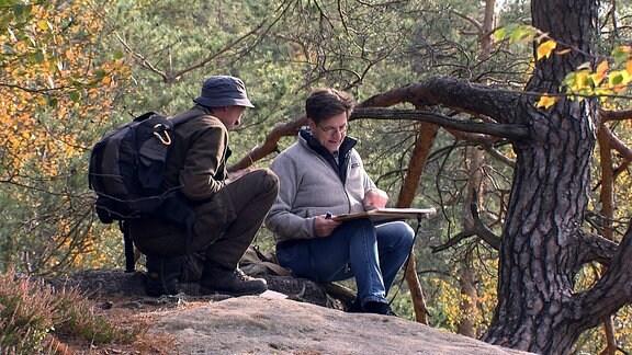 Zwei Männer sitzen auf einem Stein und schauen auf eine Karte