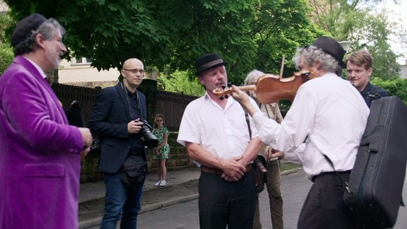 Musikant spielt vor Personen auf einer Straße.