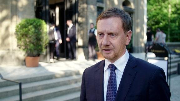 Ministerpräsident von Sachsen, Michael Kretschmer, steht vor einem Gebäude und spricht während eines Interviews.