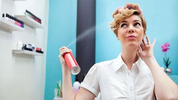 Symbolbild - Frau macht sich die Haare due Haare schön