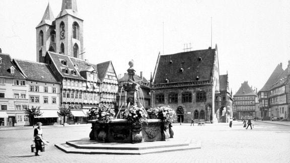 Frau an Brunnen auf Halberstadts Holzmarkt.