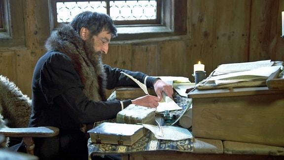 Ein Mann schreibt mit Feder in einer Schreibstube.