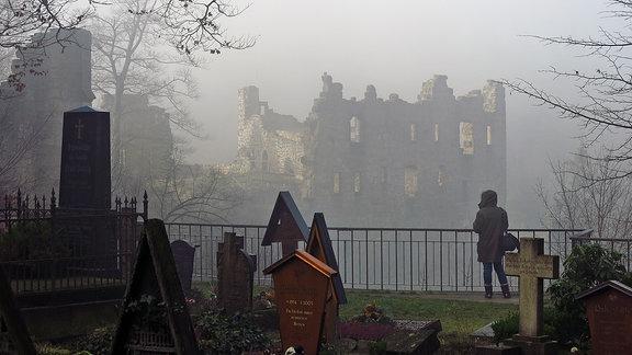Blick von einem Friedhof auf eine Ruine im Nebel