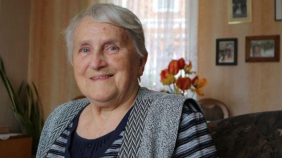 Eine ältere Frau blickt in die Kamera