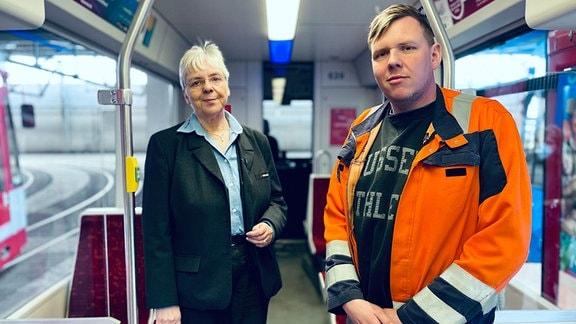 Weißhaarige Frau in Anzug und Bluse und ein junger blonder Mann in orangener Arbeitskleidung stehen in einer Straßenbahn nebeneinander
