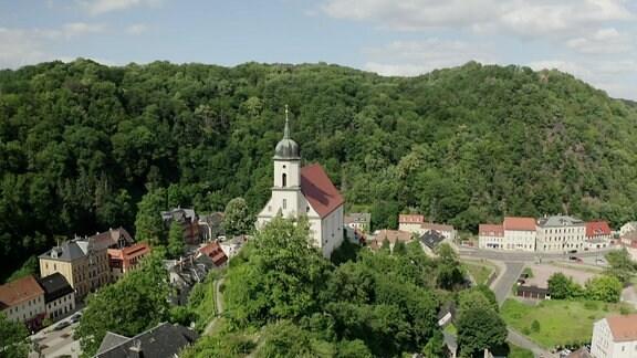 Ort von bewaldeten Hügeln umgeben