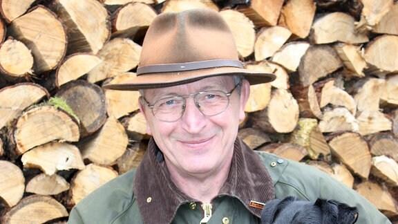 Friedrich Noltenius mit Hund vor Wand aus Holzscheiden