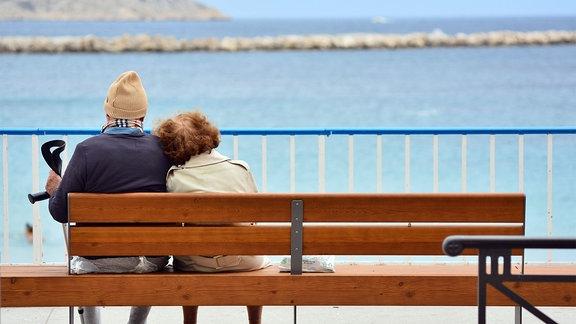 Älteres Ehepaar sitzt auf Bank am Strand.