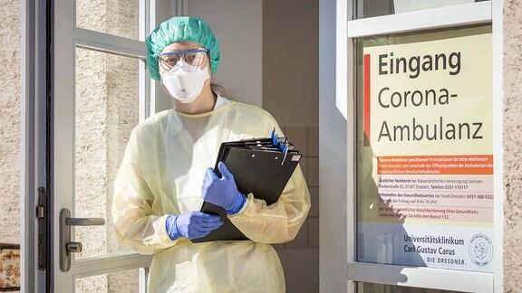 Eine Infektiologin in Schutzausrüstung steht mit vorgefertigten Fragebögen in der Eingangstür der Corona-Ambulanz an der Uniklinik Dresden.