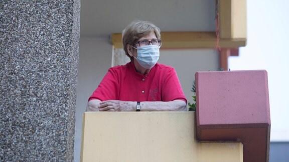 Eine Frau mit Mundschutz steht auf einem Balkon