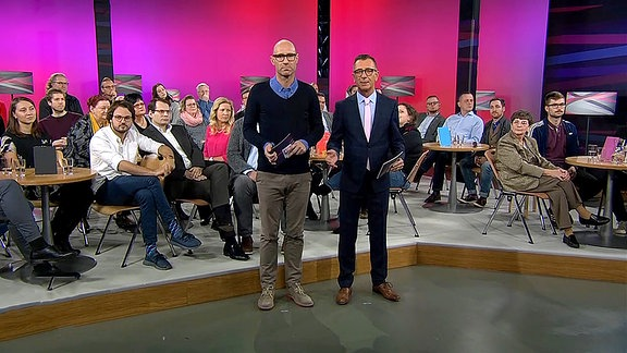 Die Moderatoren stehen nebeneinander im Studio, hinter ihnen sitzt das Publikum an mehreren runden Tischen.