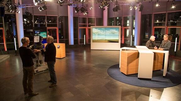 In einem Fernsehstudio stehen verschiedene Kulissen. An einem Tisch stehen zwei Männer. Zwei andere Männer stehen einige Meter entfernt davon vor einer Kamera und unterhalten sich.