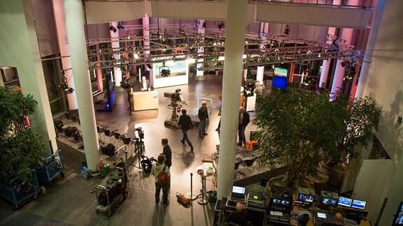 Das Foyer des MDR Landesfunkhauses in Erfurt. In dem großen Raum stehen Kulissen, Kameras und Möbel. Mehrere Menschen laufen in dem Raum herum.