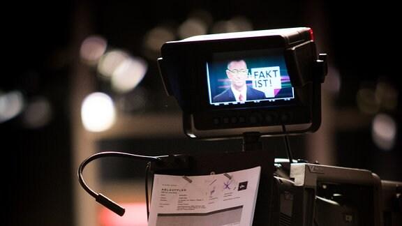Im Sucher einer Fernsehkamera ist das Profil eines Moderators zu sehen. An der Kamera ist ein weißer Zettel mit Notizen befestigt, ein Kameramann blickt in den Sucher.
