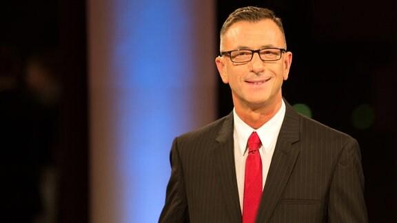 Ein dunkelhaariger Mann in Anzug und roter Krawatte und mit Brille blickt in eine Kamera und lächelt.