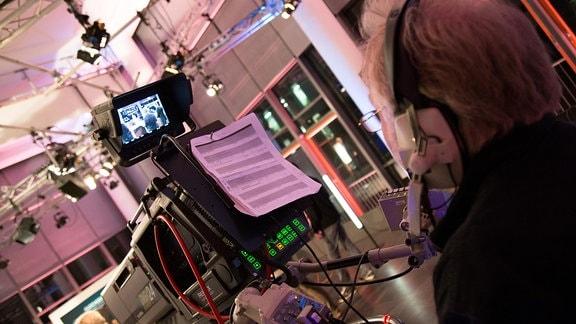 Ein Kameramann schaut durch den Sucher einer Fernsehkamera.